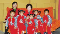 翟桂荣主任与经她接生的五胞胎,现已七周岁的五个活泼可爱的孩子在一起。
